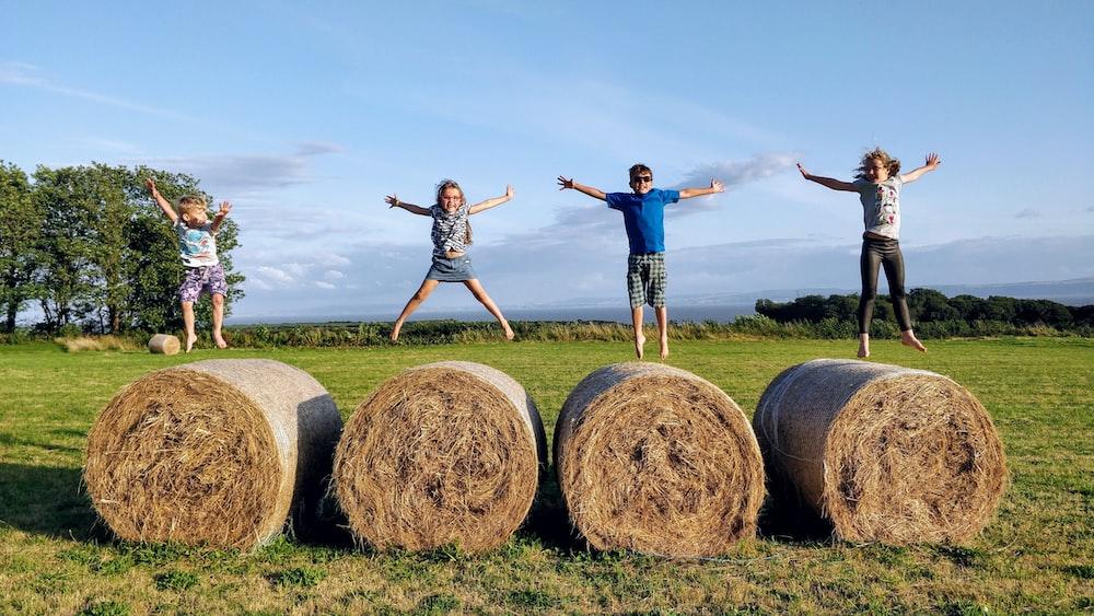 man in blue denim jeans standing on brown hays during daytime