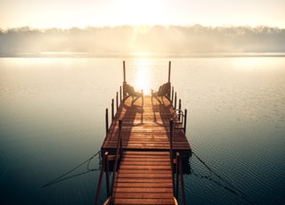 brown wooden dock on body of water during daytime