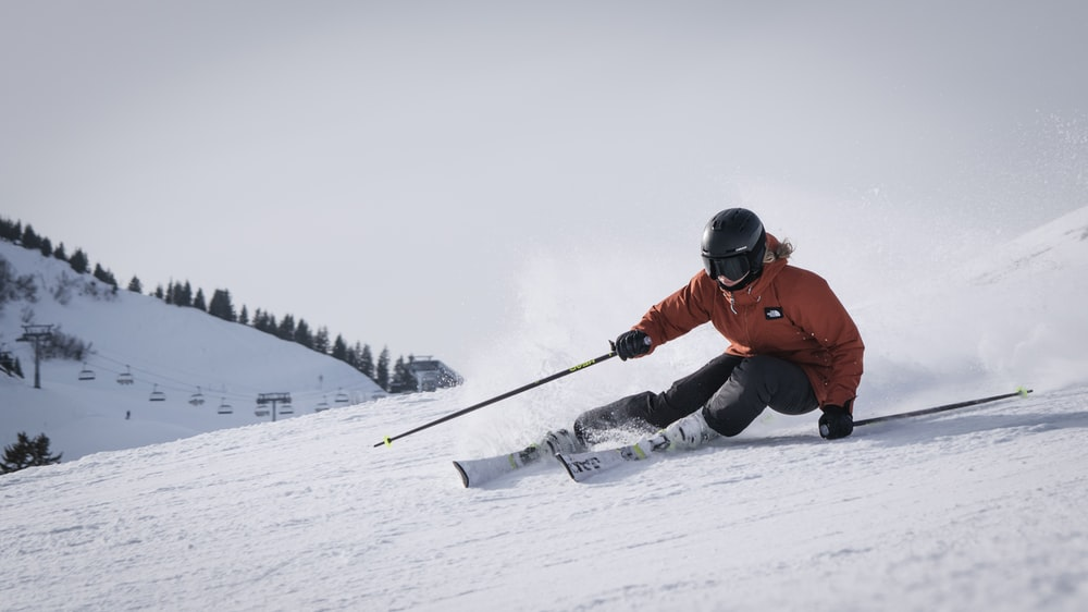 person in red jacket and black pants riding on snow board during daytime