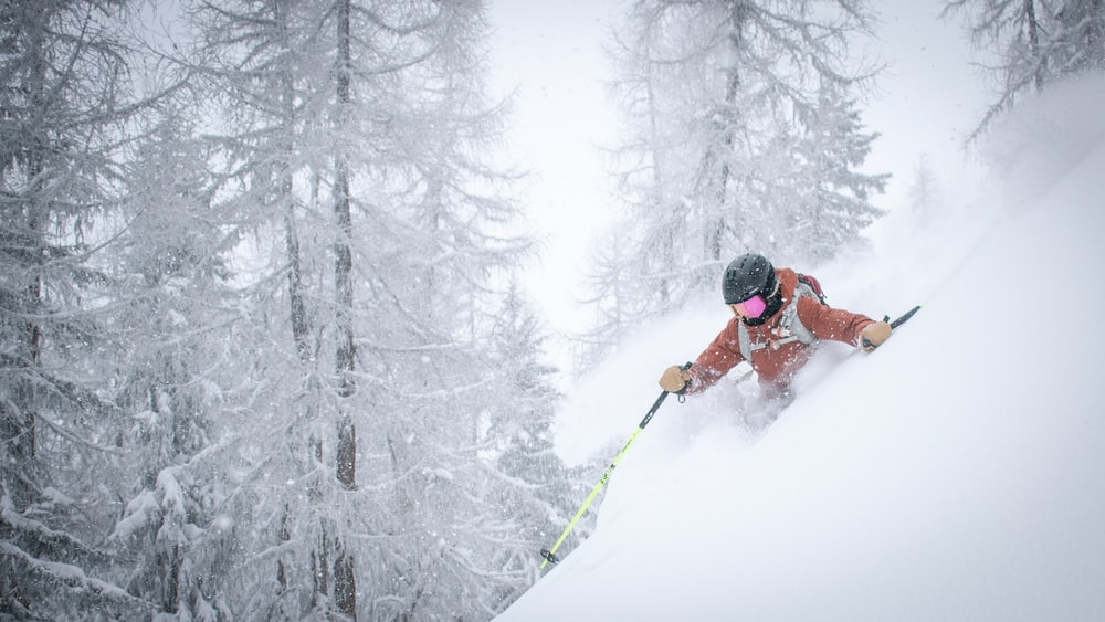 person in red jacket and black pants riding on ski blades on snow covered ground during
