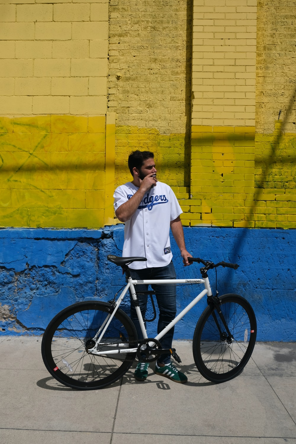 man in white shirt and black pants riding on black bicycle