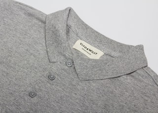 gray polo shirt on white table
