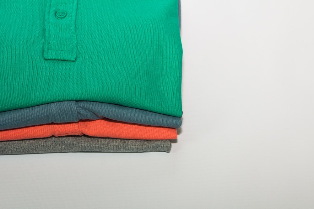 green polo shirt on white table