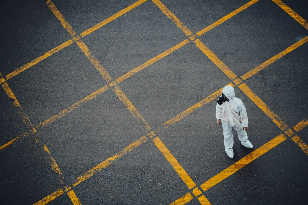 man in white thobe walking on grey and yellow concrete pavement