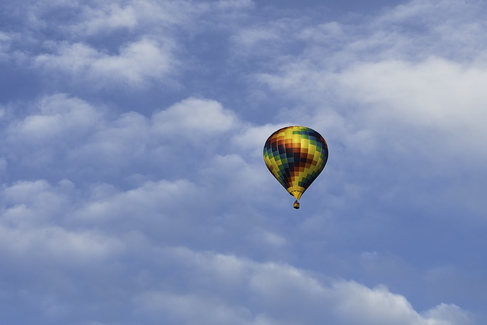 hot air balloon in mid air under cloudy sky during daytime
