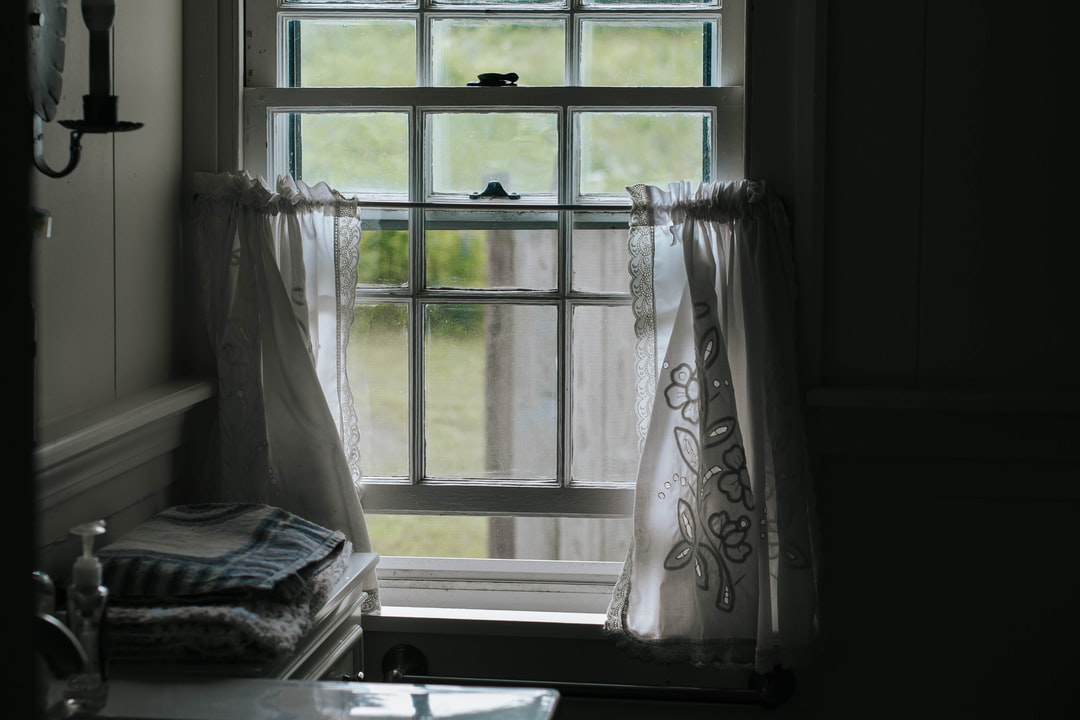 A Window With White Embroidered Curtains Lit By Natural Light.  - unsplash