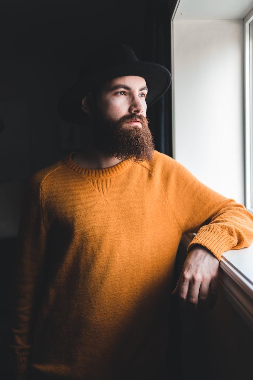 man in orange turtleneck sweater and black fedora hat