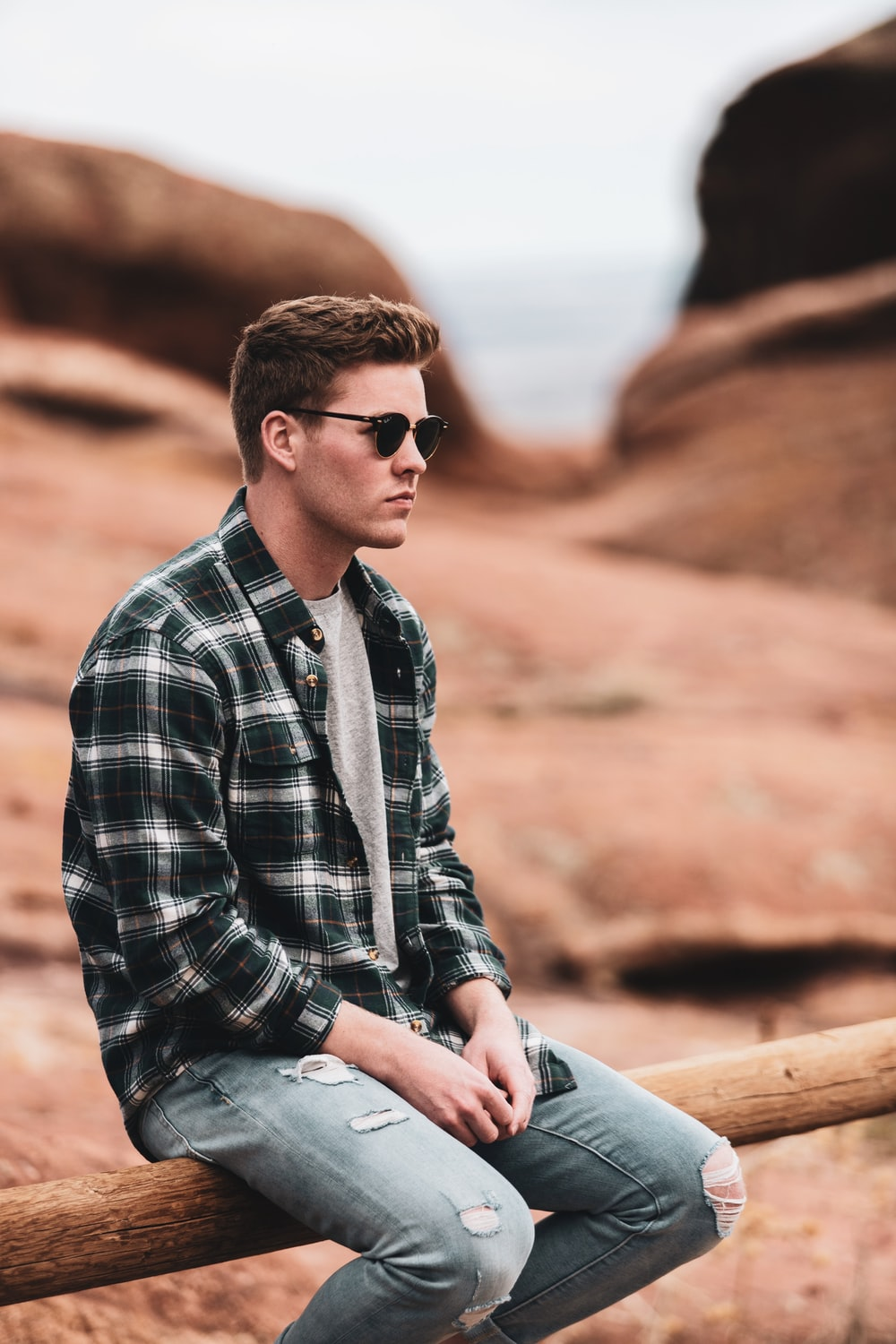 man in black and white plaid dress shirt wearing black sunglasses sitting on brown rock during