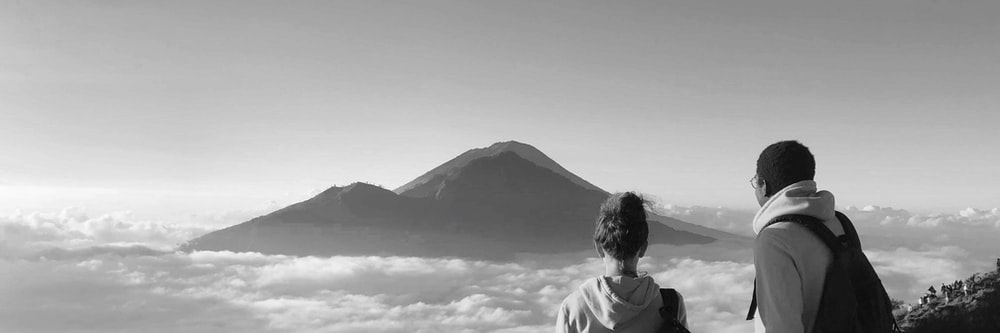 grayscale photo of man in white shirt looking at mountain