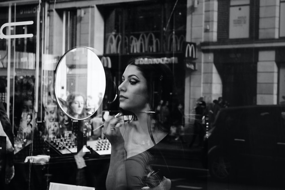grayscale photo of woman holding magnifying glass