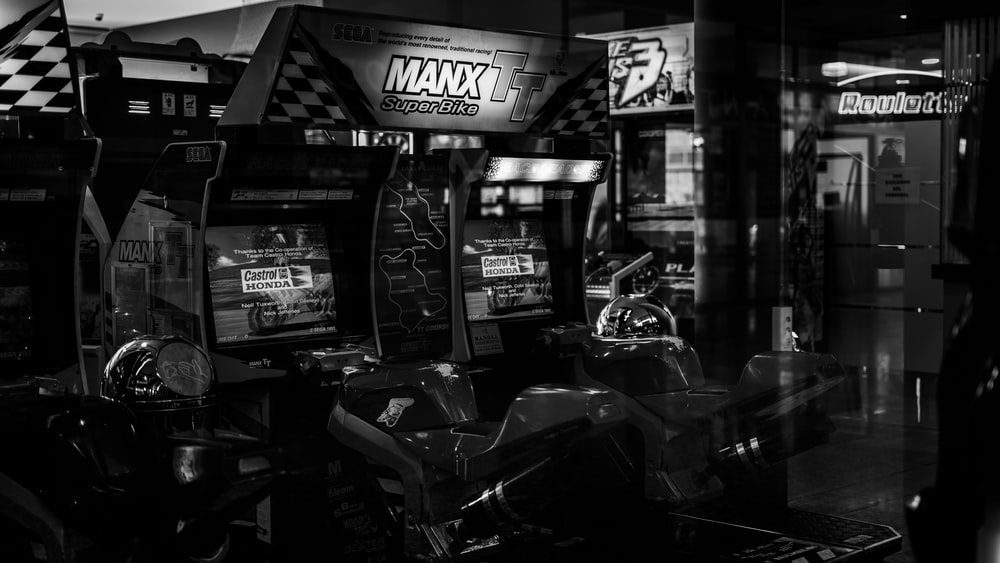 grayscale photo of motorcycle parked near store
