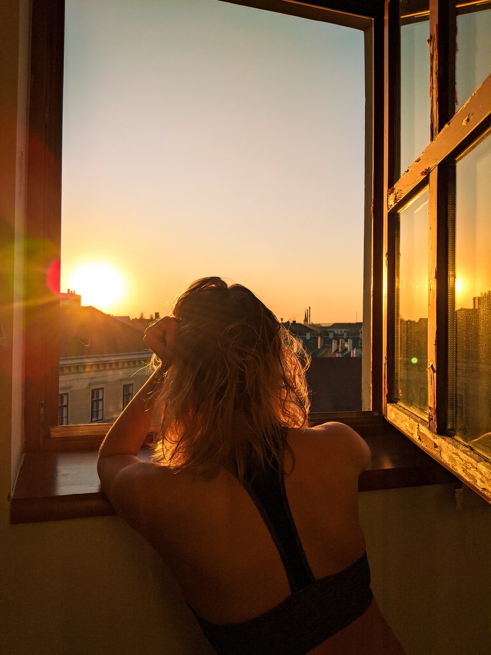 woman in black tank top sitting on brown wooden bench during sunset