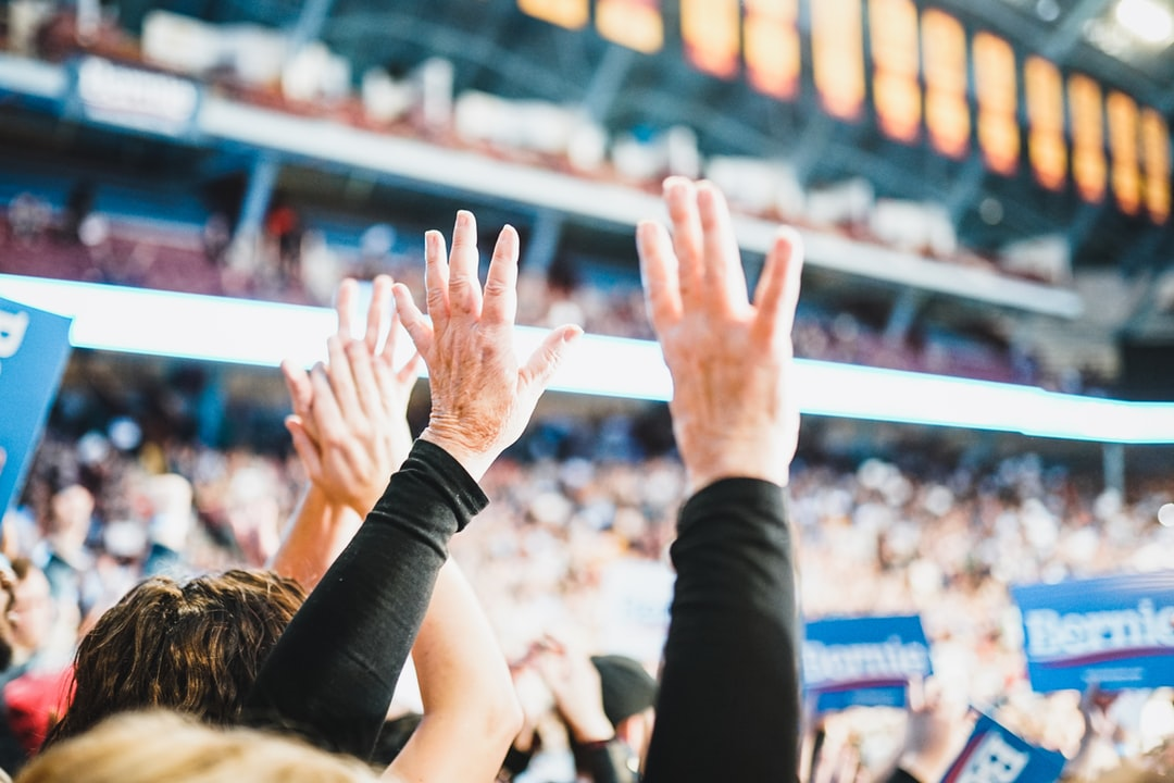 Person In Black Long Sleeve Shirt Raising Hands - unsplash