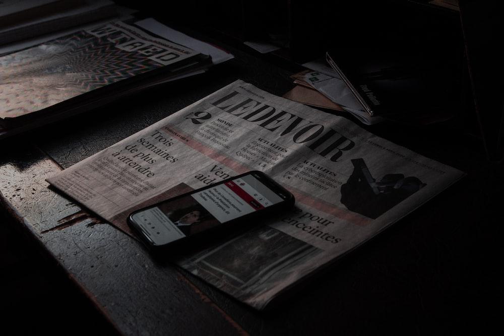 black smartphone on newspaper beside newspaper