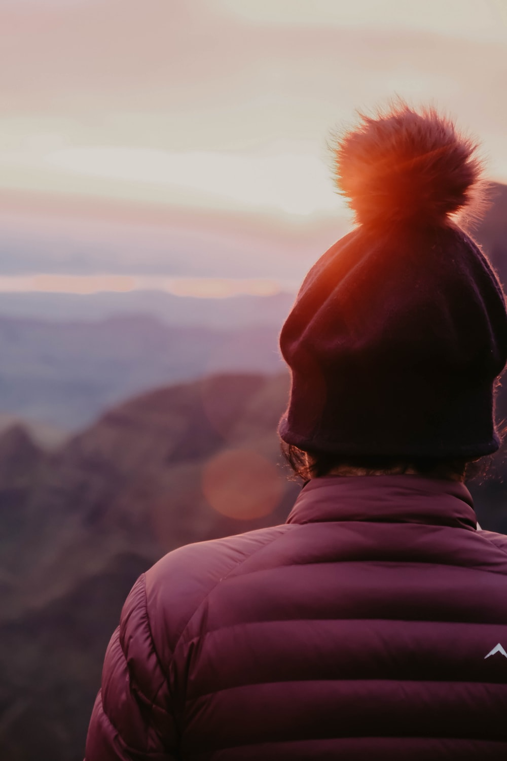 person in black knit cap and pink hoodie looking at the mountains during daytime