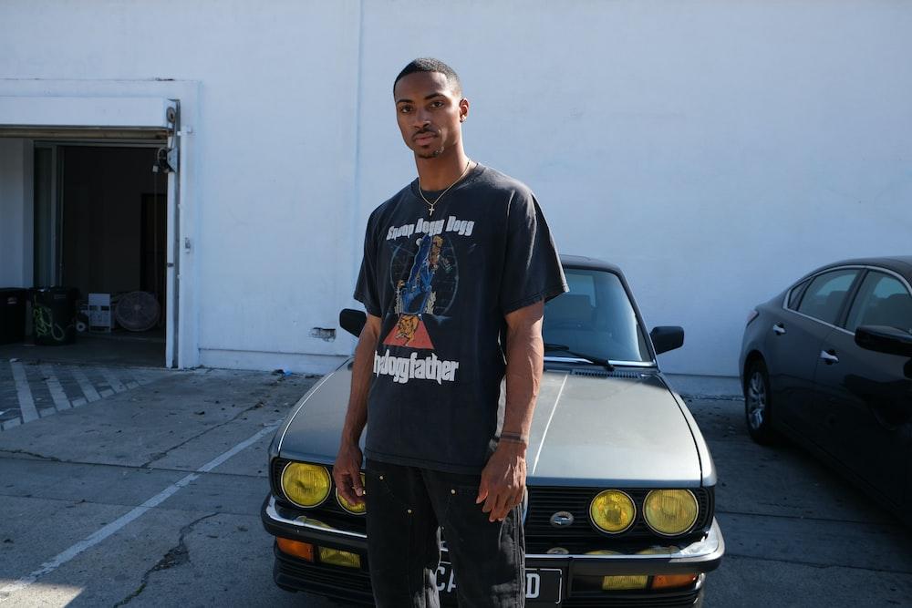 man in black crew neck t-shirt standing beside yellow car