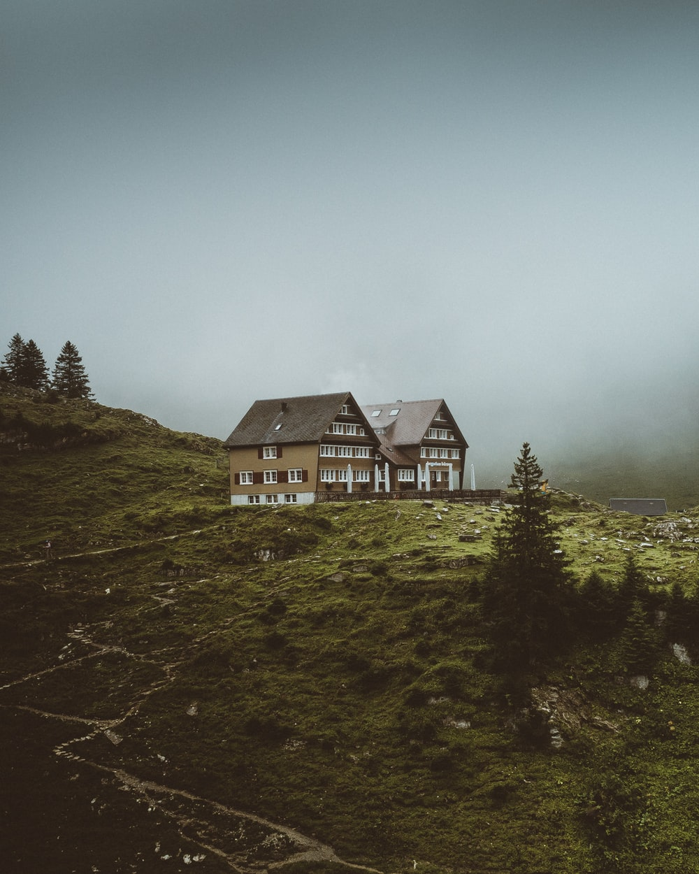 white and black house on green grass field under gray sky