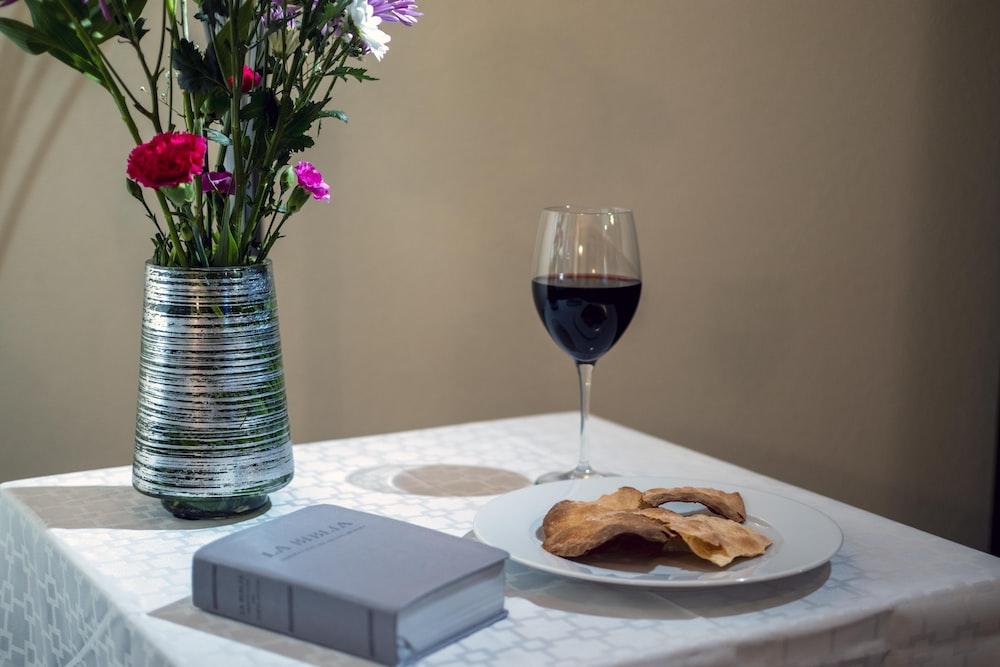 bread on white ceramic plate beside purple flowers in clear glass vase