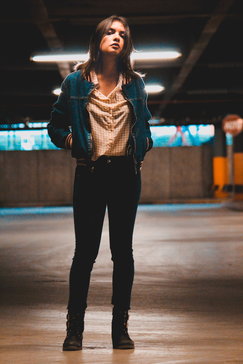 woman in gray jacket and black pants standing on gray pavement