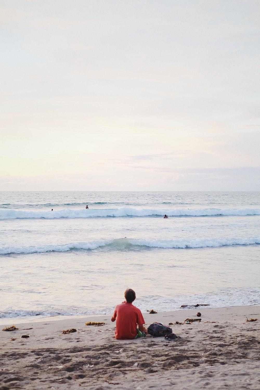 man in red shirt sitting on beach during daytime