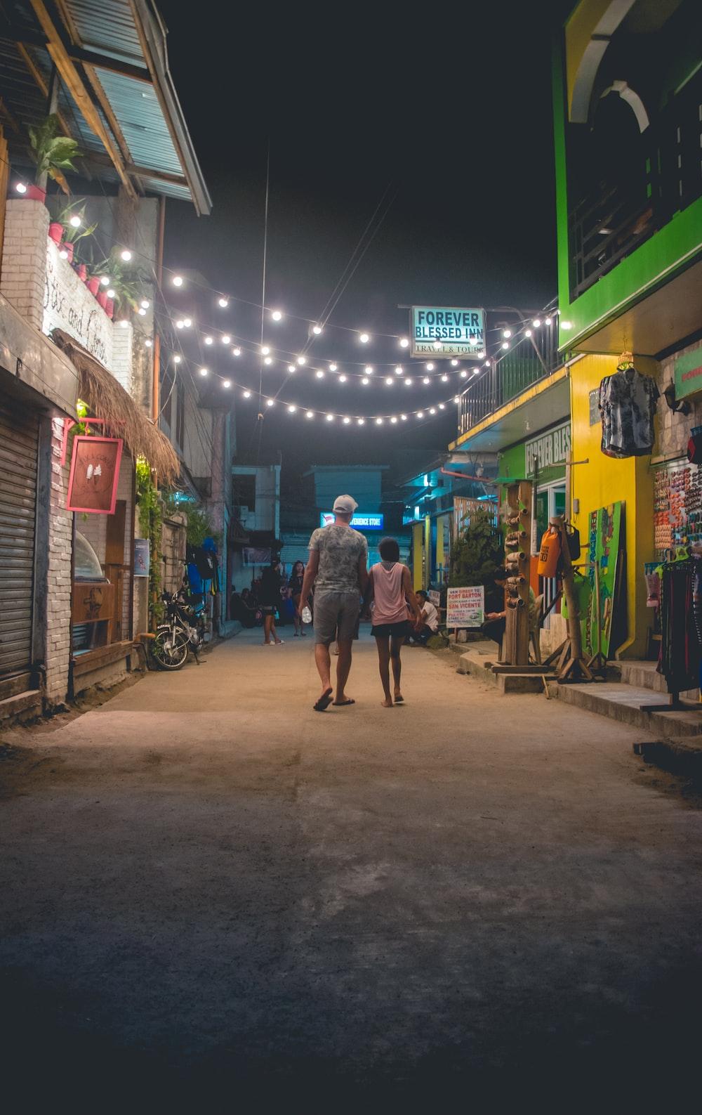 man in gray coat walking on street during nighttime