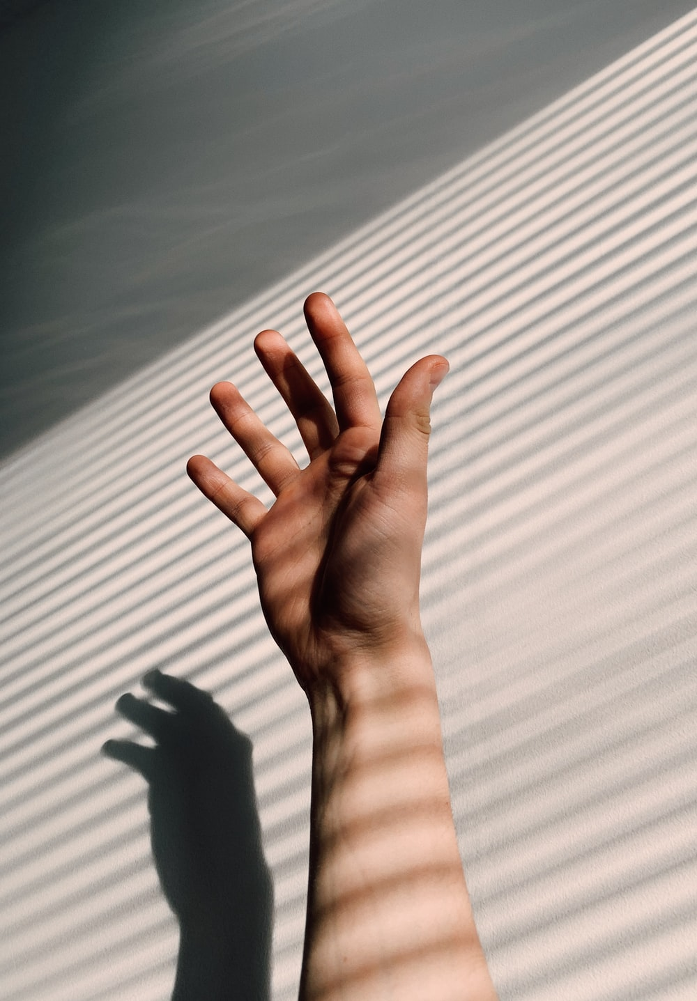 persons left hand on white window blinds