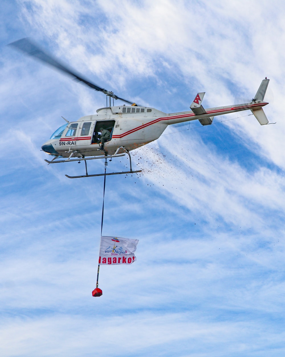 white and red helicopter flying under blue sky during daytime
