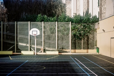 white basketball hoop near green trees during daytime basketball court teams background