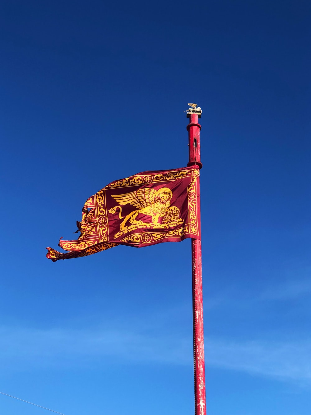 red and gold flag under blue sky during daytime