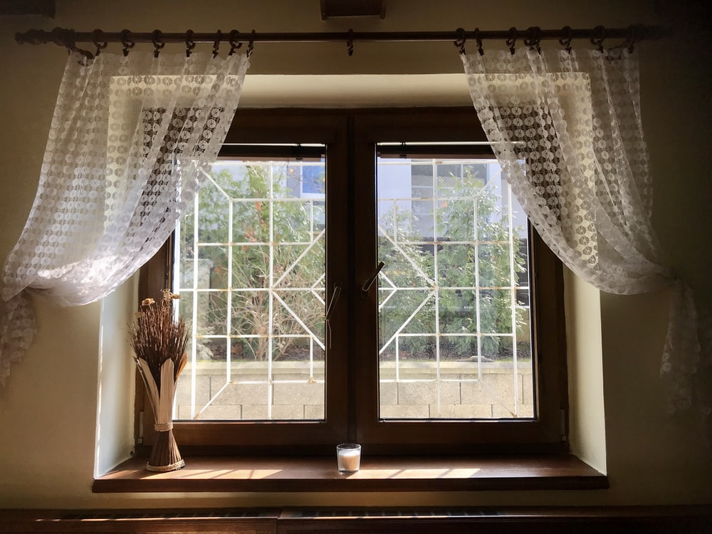 white floral window curtain on white wooden framed glass window