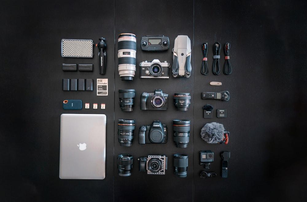 silver macbook black dslr camera and black dslr camera
