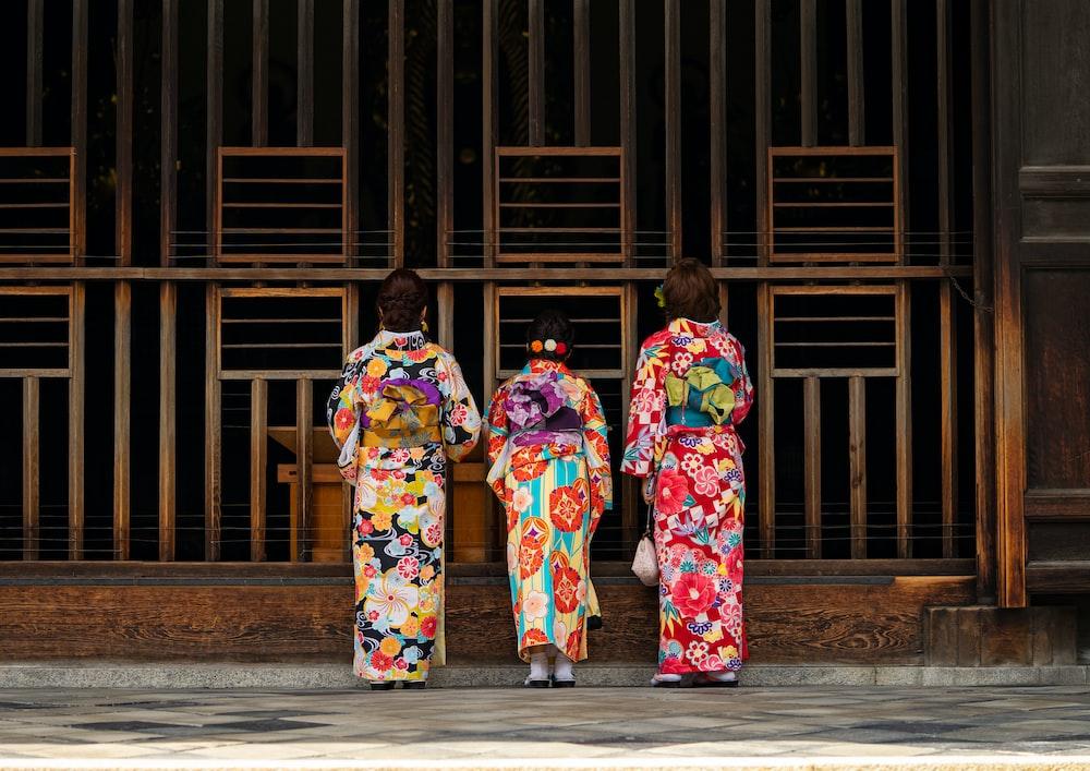 2 women in kimono standing on sidewalk during daytime