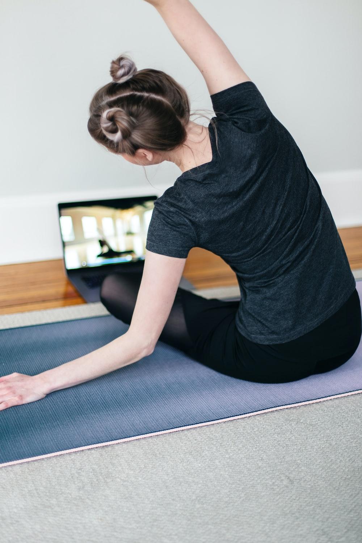 woman in black t-shirt and black pants lying on black yoga mat