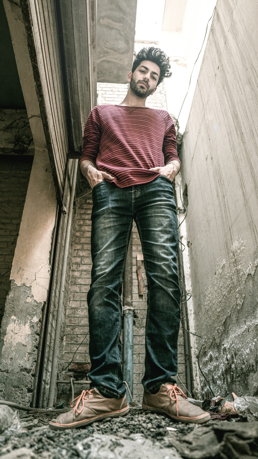 man in red and white striped shirt and blue denim jeans standing on stairs