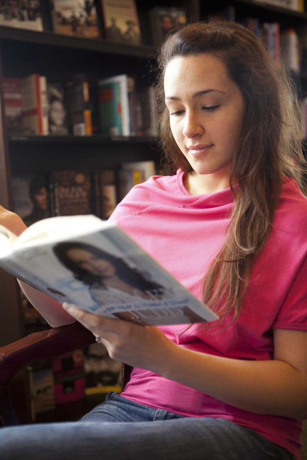 woman in pink crew neck t-shirt holding white book