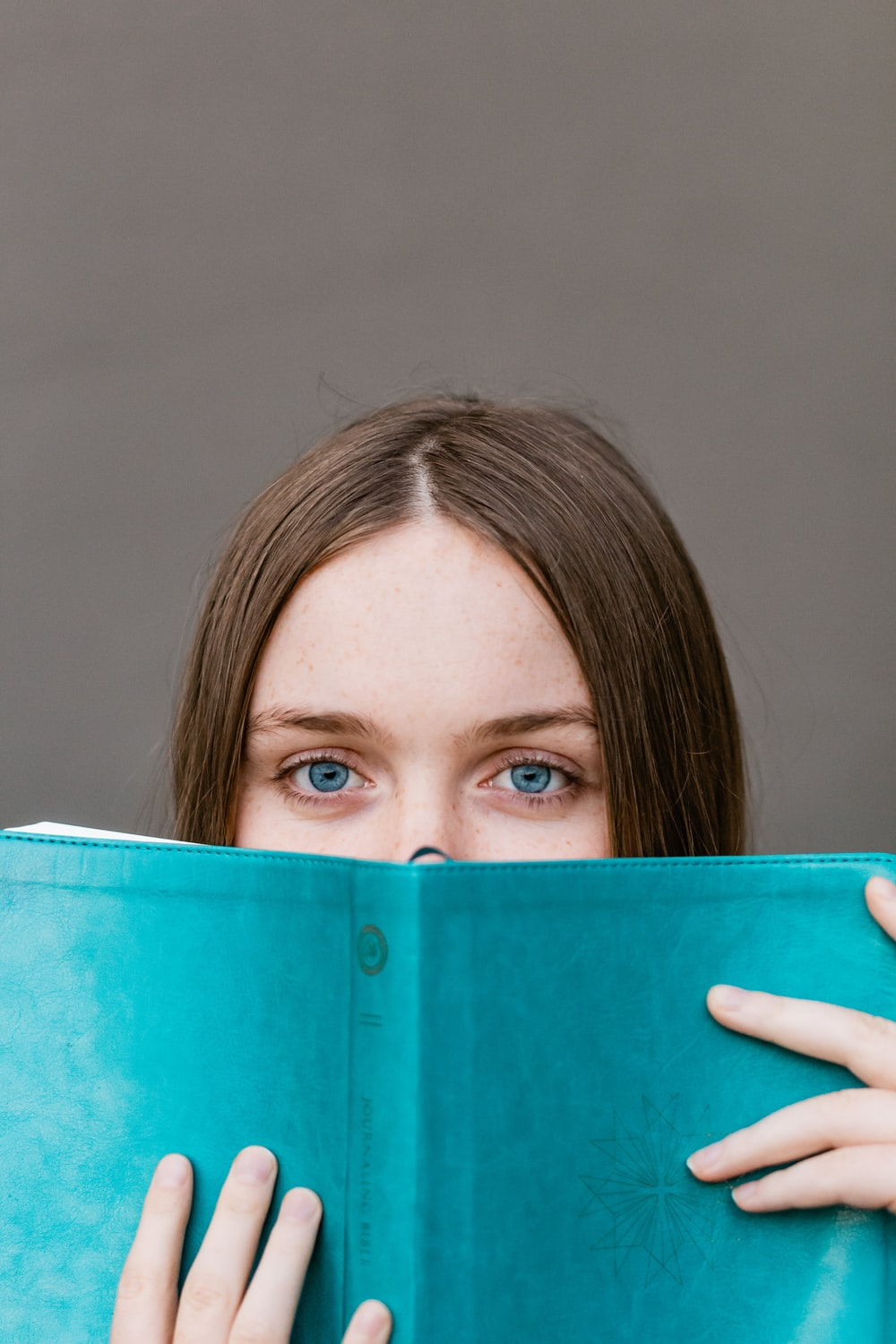 woman covering her face with teal book