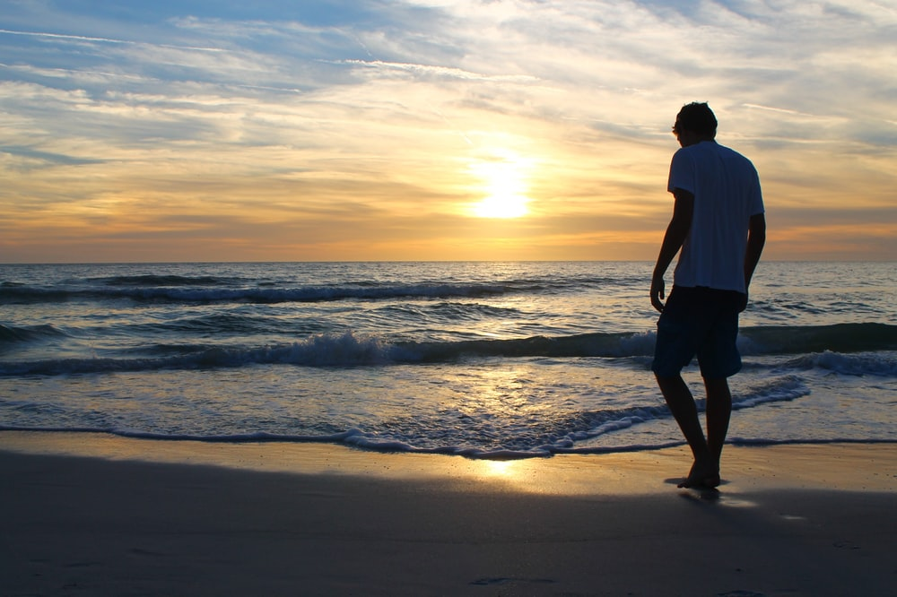 man in white t-shirt and black shorts standing on seashore during sunset