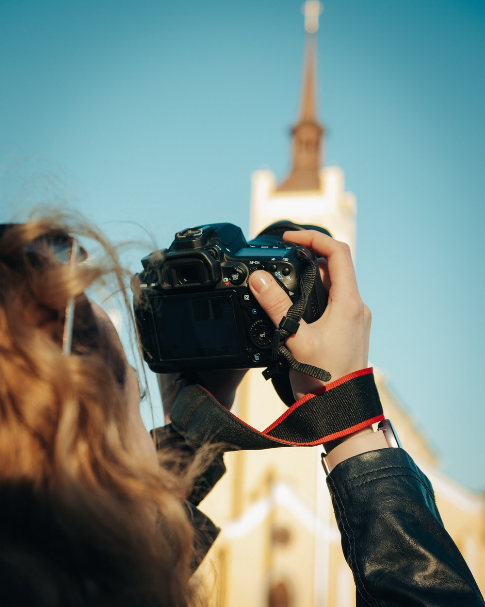 woman in black jacket holding black dslr camera