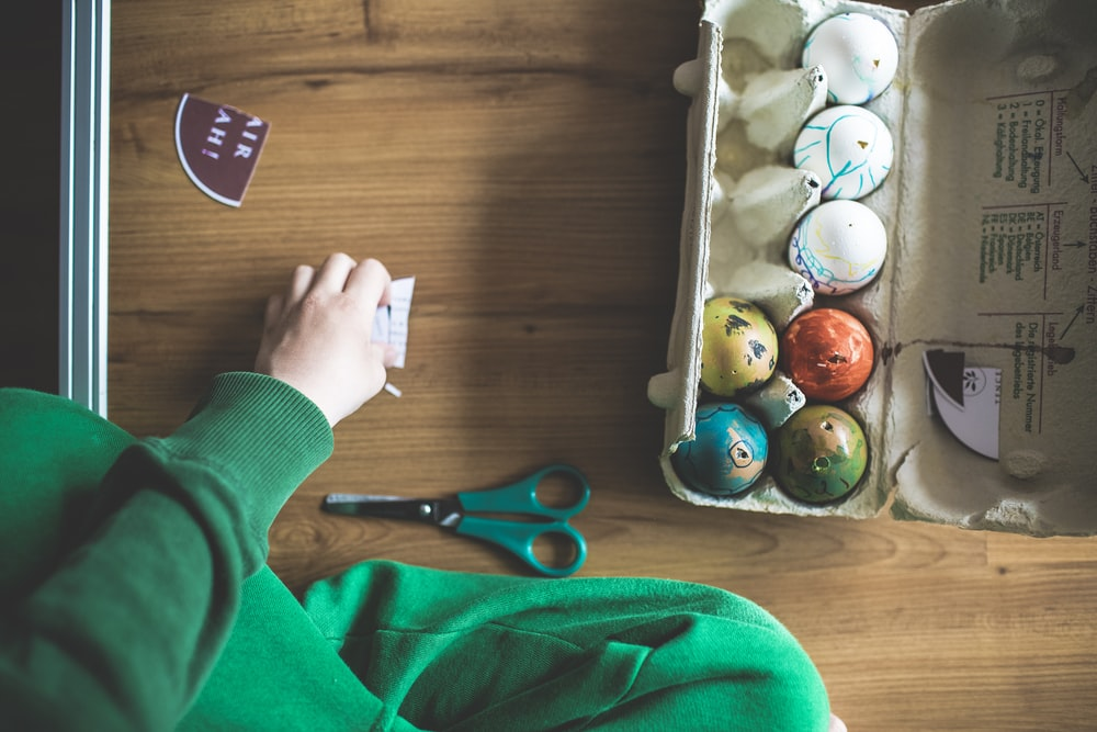 person holding white egg tray with black scissors