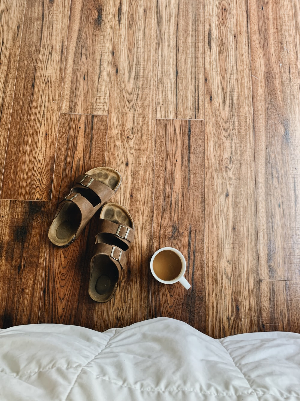 brown and black sandals on brown wooden floor