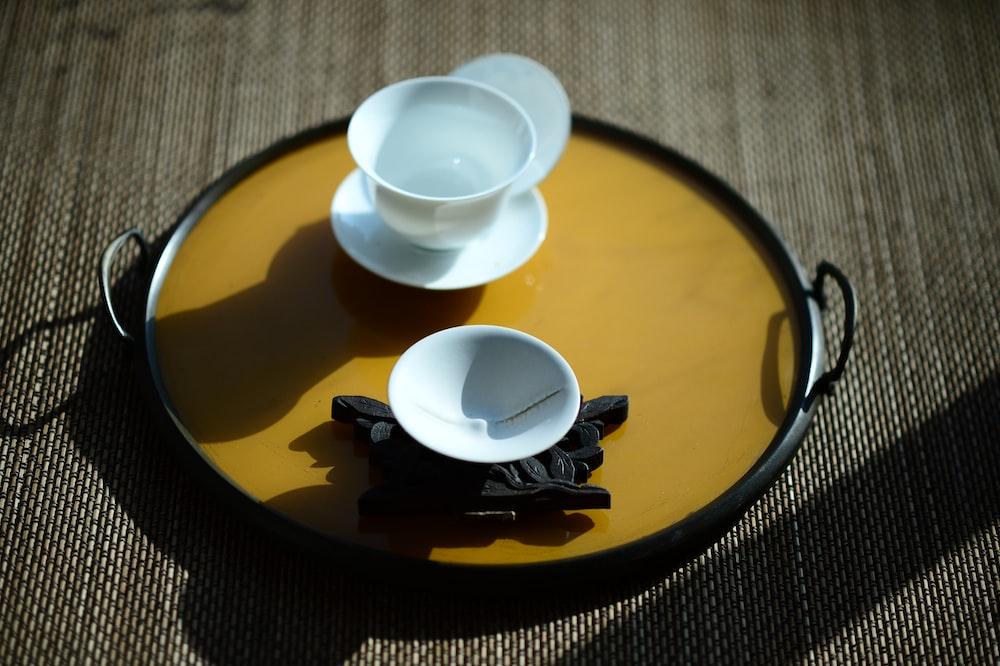 white ceramic teacup on brown ceramic plate