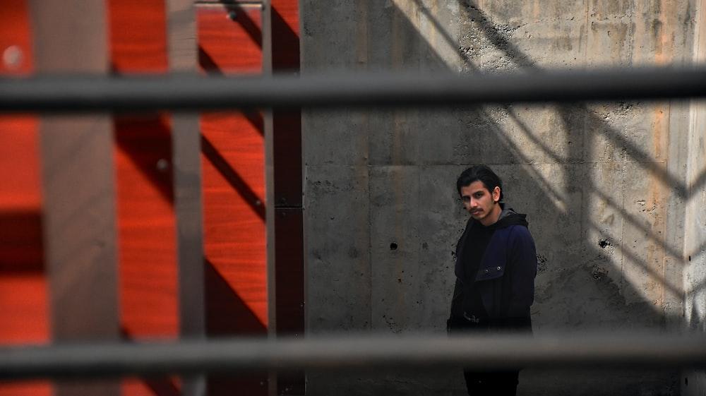 man in black jacket standing beside red metal gate
