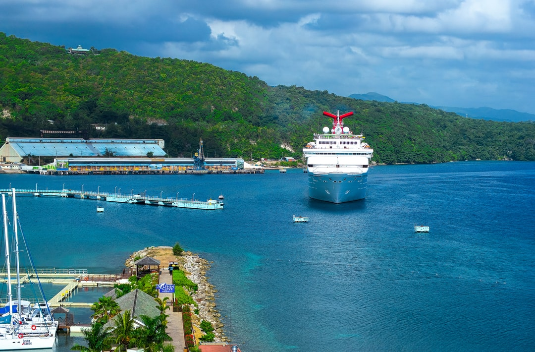 A cruise ship makes its way to the shore in Ochos Rios Jamaica on a cloudy day.