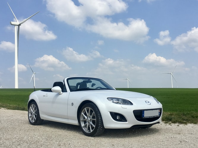 White Mazda Miata in country with windmills in background