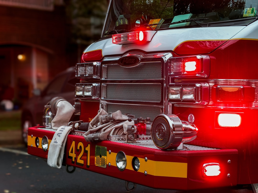 A fire truck carrying first responders and displaying emergency lights - parked outside of an apartment building in Fairfax Virginia.