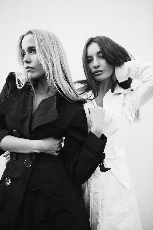 woman in black coat standing beside woman in white coat