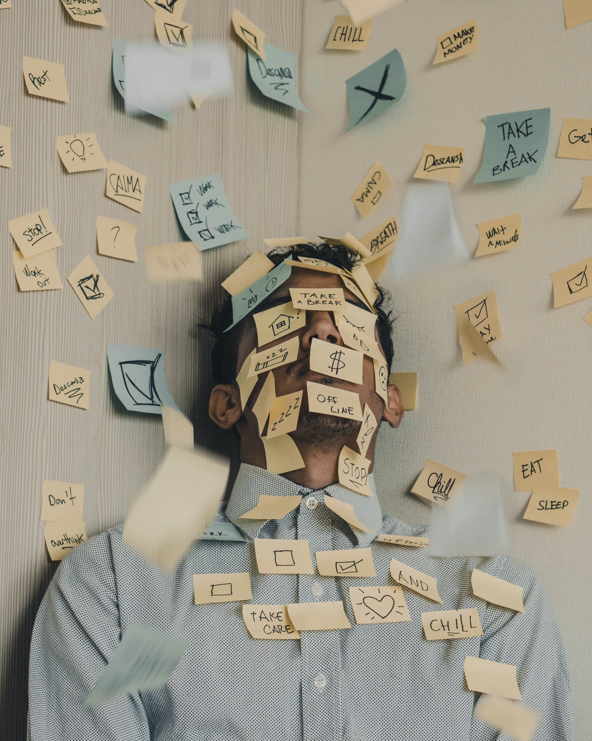 Young man covered in sticky notes, work overload
