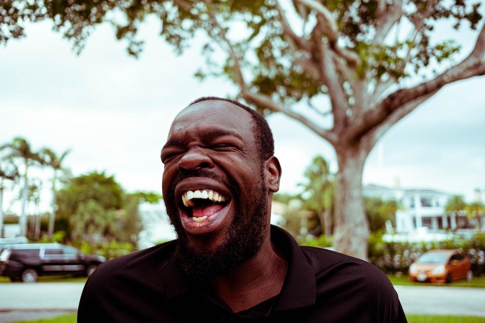 man in black polo shirt smiling