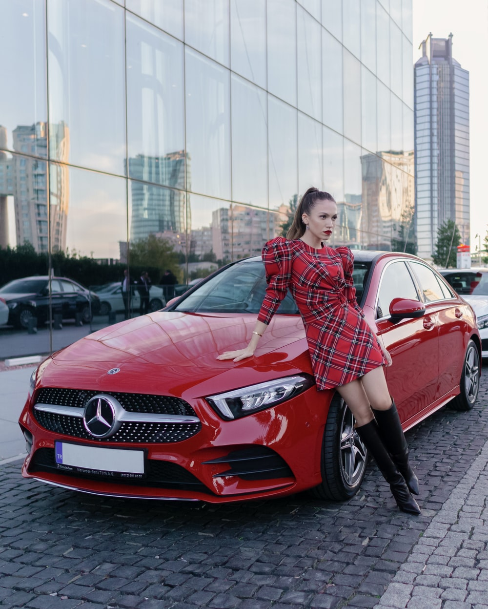 woman in red and black plaid dress shirt standing beside red mercedes benz car