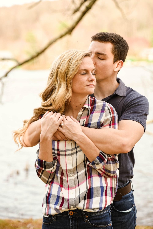 man in blue crew neck t-shirt kissing woman in plaid shirt